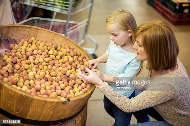 Mother and daughter at supermarket shopping for lychees