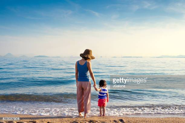 mother and daughter at the beach - japanese mom stock photos and pictures