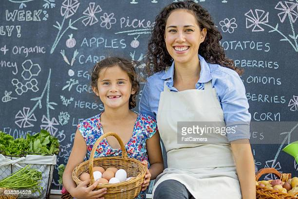 mother and daughter at their farm stand - agricultural fair stock photos and pictures