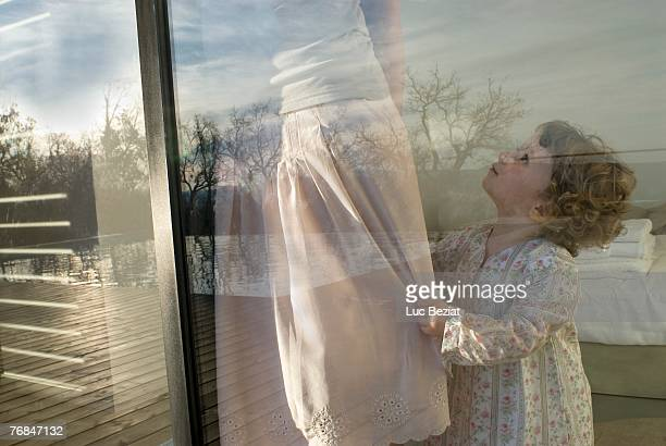 Mother and daughter (18-24 months) at window.