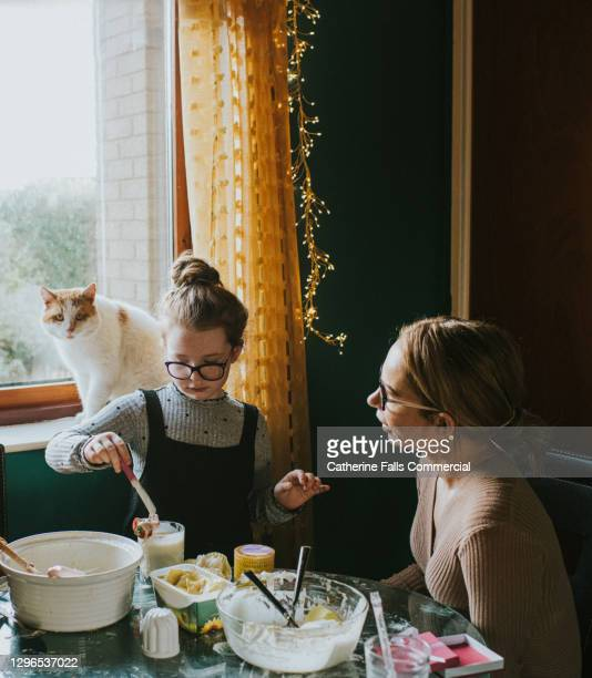 mother and daughter bake together in a quiet kitchen - mother stock pictures, royalty-free photos & images