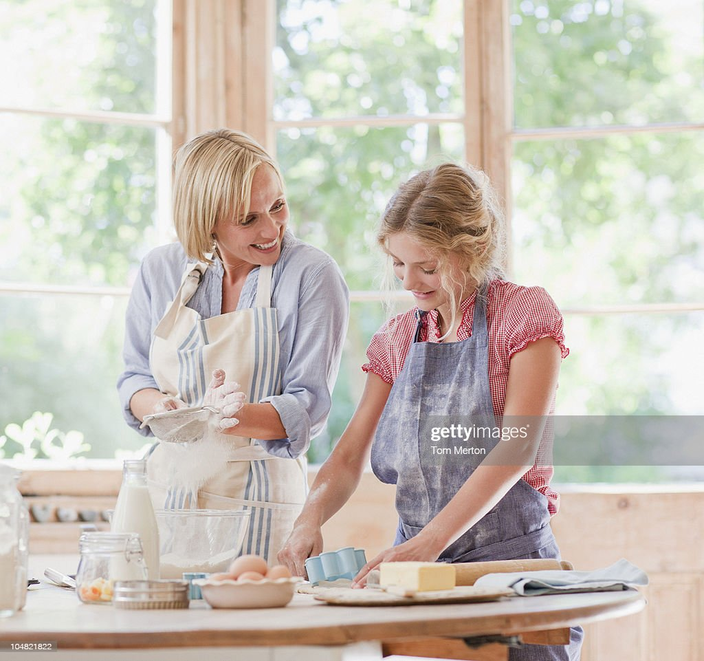 Mother and daughter baking at table in kitchen : Stock Photo