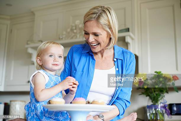 mother and daughter (12-23 months) baking cakes in kitchen - 12 23 months stock pictures, royalty-free photos & images