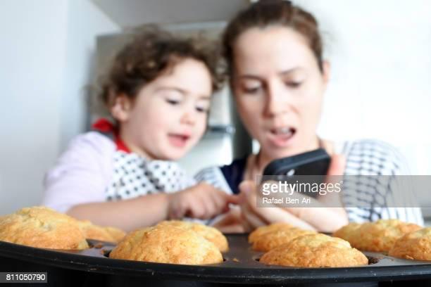 mother and daughter baking cookies - rafael ben ari stock-fotos und bilder