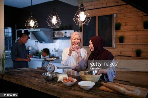 mother and daughter baking in kitchen - eid mubarak stock pictures, royalty-free photos & images