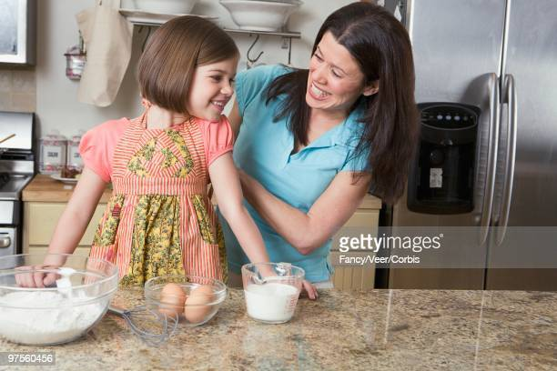 mother and daughter baking together - zakelijke kleding stock pictures, royalty-free photos & images