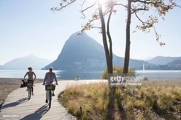 Mother and daughter bike along boardwalk,lakeshore
