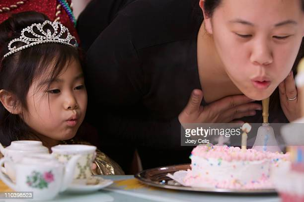 Mother and daughter blow out birthday candles