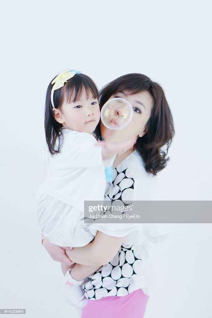 Mother And Daughter Blowing Bubble Against Wall : Stock Photo