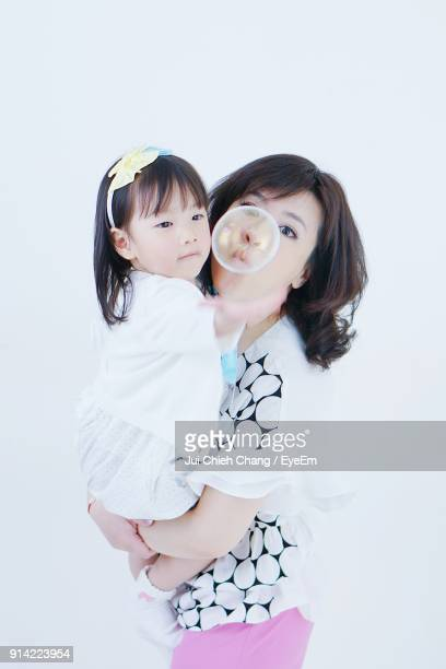 Mother And Daughter Blowing Bubble Against Wall