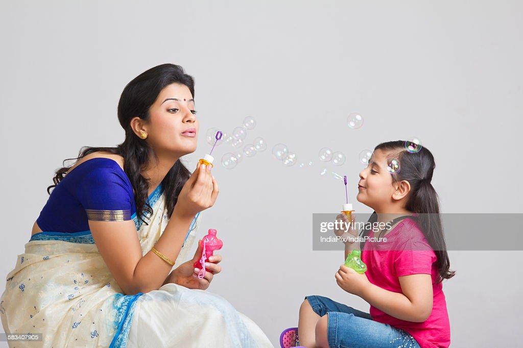 Mother and daughter blowing bubbles : Stock Photo