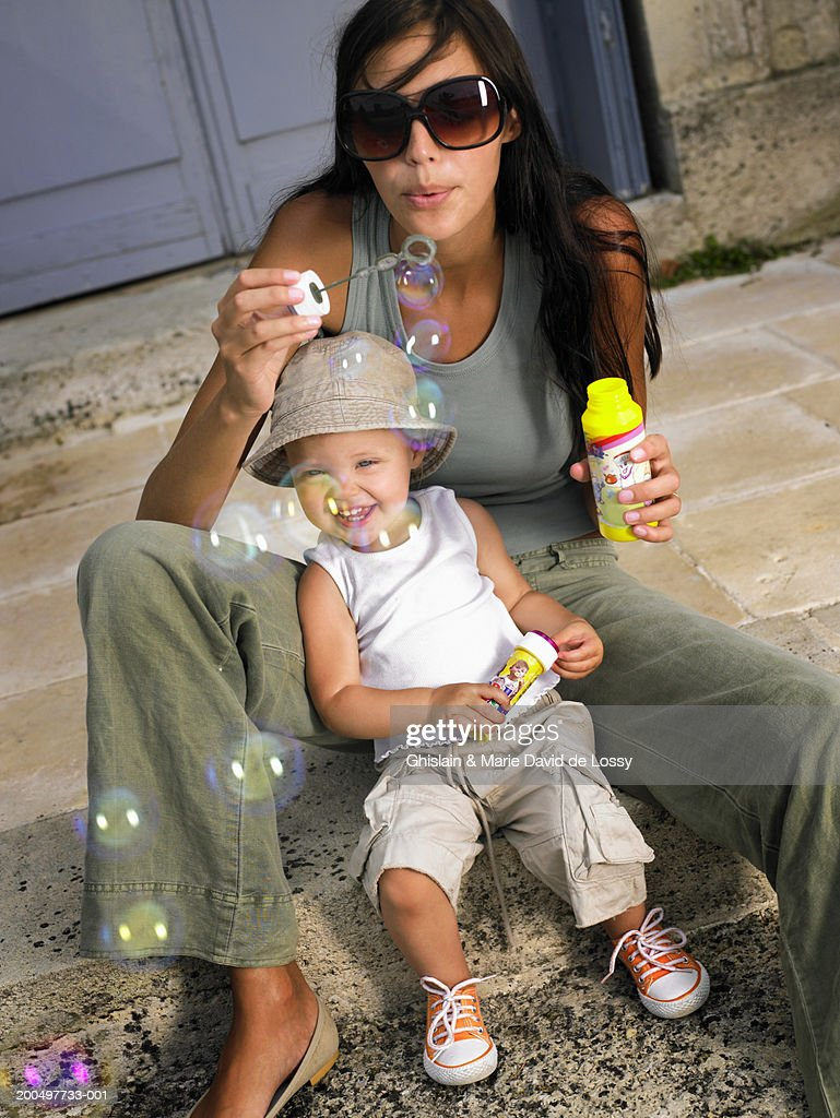 Mother and daughter (18-21 months) blowing bubbles with bubble wand : Foto de stock