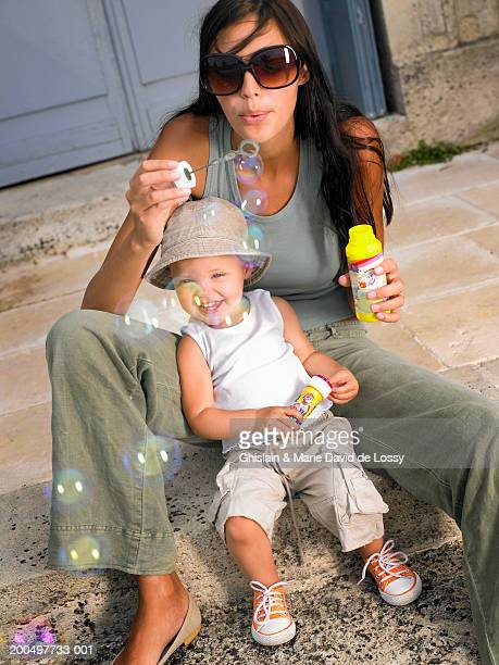 mother and daughter (18-21 months) blowing bubbles with bubble wand - 18 23 months stock pictures, royalty-free photos & images