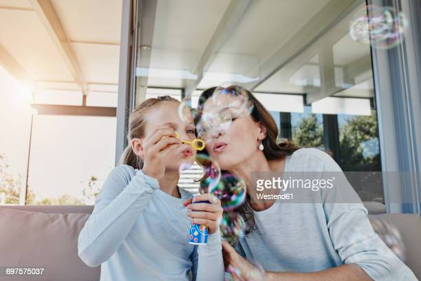 Mother and daughter blowing soap bubbles on terrace