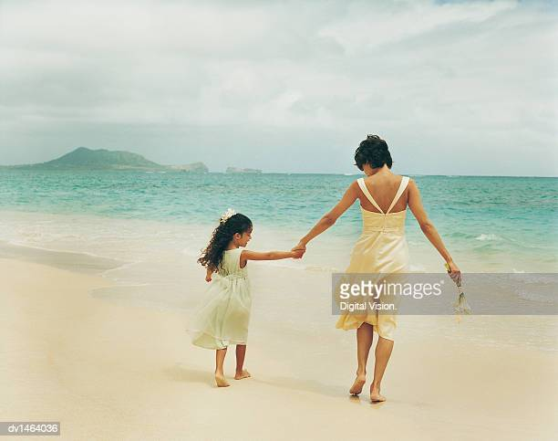 Mother and Daughter Bridesmaids Hold Hands and Walk in the Sand Towards the Sea
