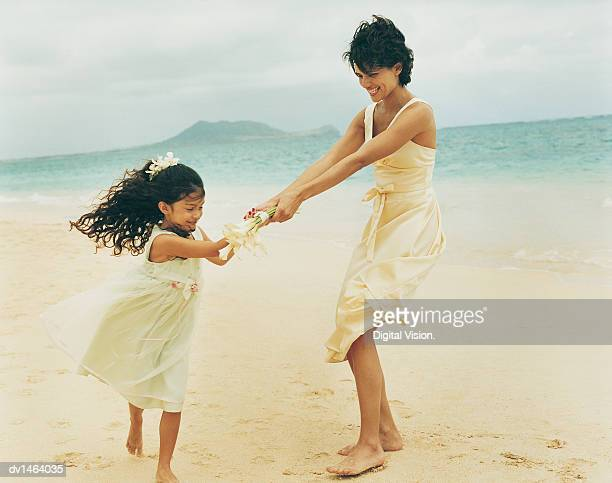 Mother and Daughter Bridesmaids Play in the Sand at the Waters Edge on a Beach