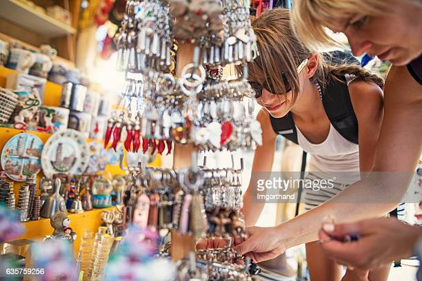 Mother and daughter browsing souvenirs at street market in Pisa