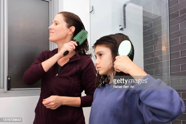 mother and daughter brushing hair together - rafael ben ari stockfoto's en -beelden