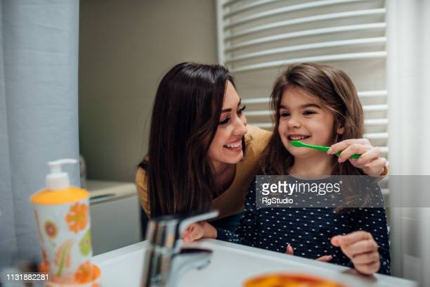 mother and daughter brushing teeth - human teeth stock pictures, royalty-free photos & images