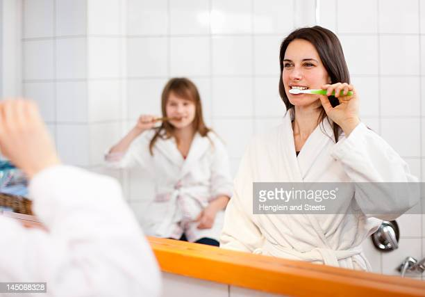 mother and daughter brushing teeth - girl in mirror stock photos and pictures