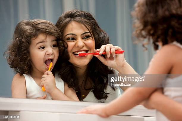 Mother and daughter (2-3) brushing teeth