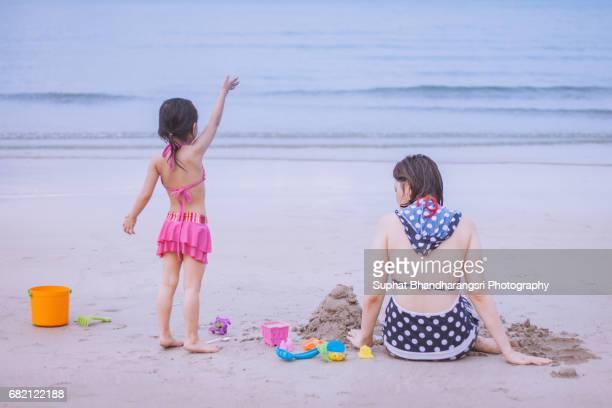 Mother and daughter building sand castle together
