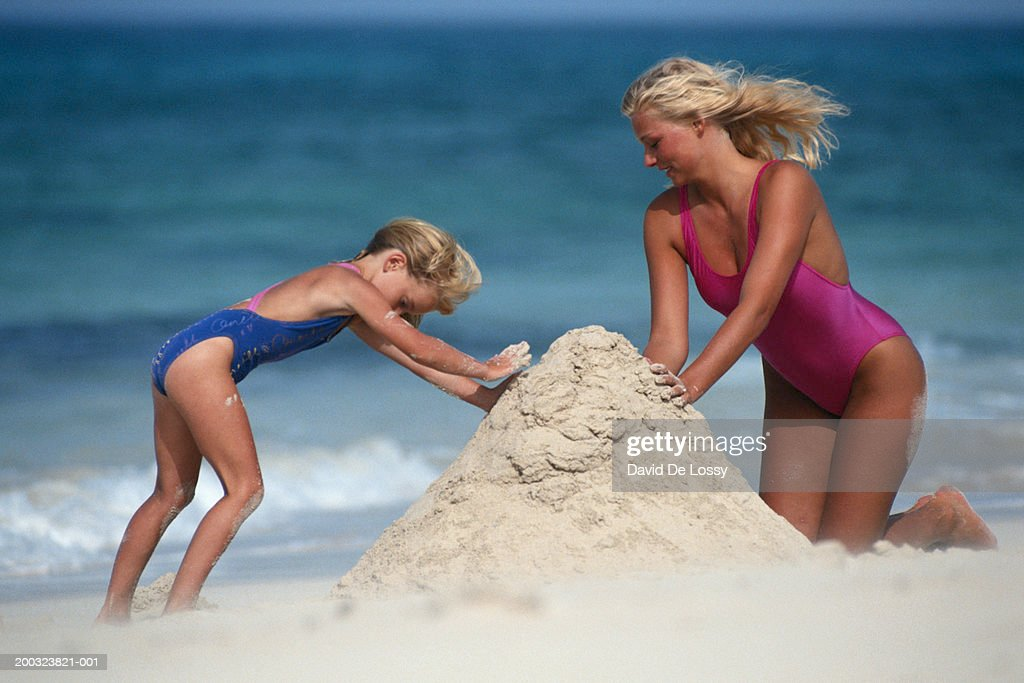 Mother and daughter (4-5) building sandcastle : Stock Photo