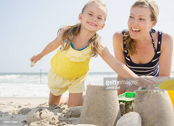 Mother and daughter building sandcastle together