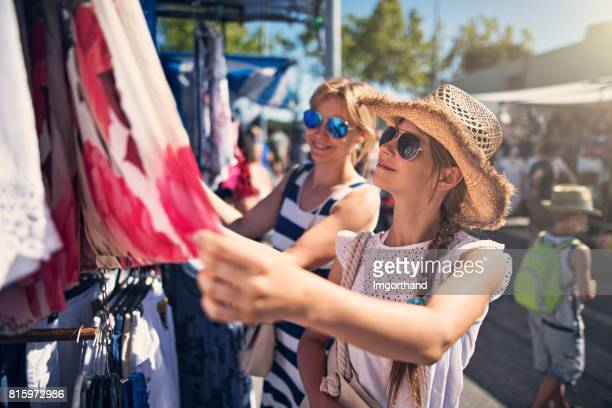 mother and daughter buying clothes  on flea market in andalusia, spain - cowboy hat stock pictures, royalty-free photos & images