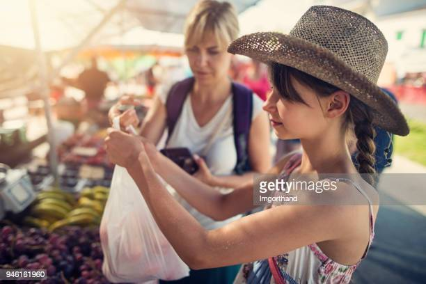 mother and daughter buying fruit at the majorcan farmer's market - local produce stock pictures, royalty-free photos & images