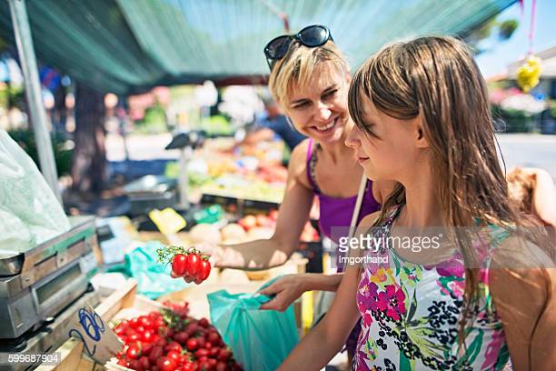 Mother and daughter buying tomatoes at the Italian farmer's market