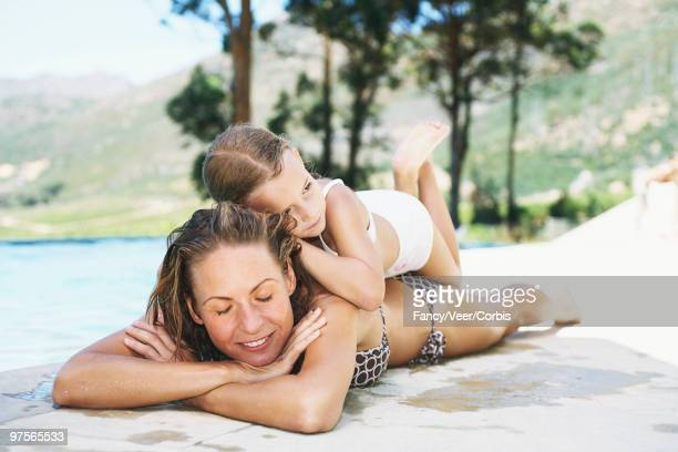 mother and daughter by a pool - woman lying on stomach with feet up stock photos and pictures