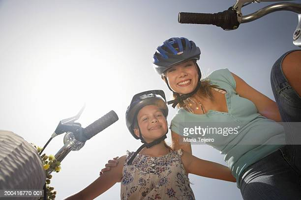 Mother and daughter (9-11) by bicycles, portrait, low angle view