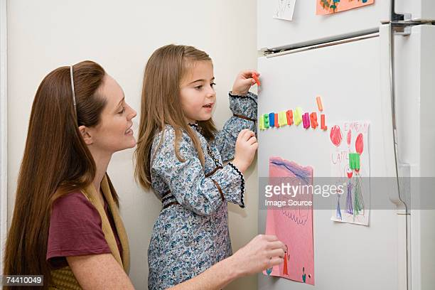 Mother and daughter by refrigerator