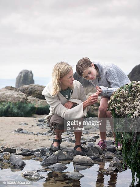 Mother and daughter (12-13) by tide pool