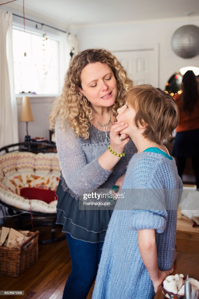 Mother and daughter candid moment while decorating for Christmas at home. : Stock Photo