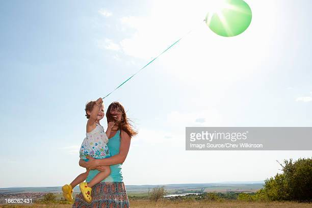 mother and daughter carrying balloon - 1歳以上2歳未満 ストックフォトと画像