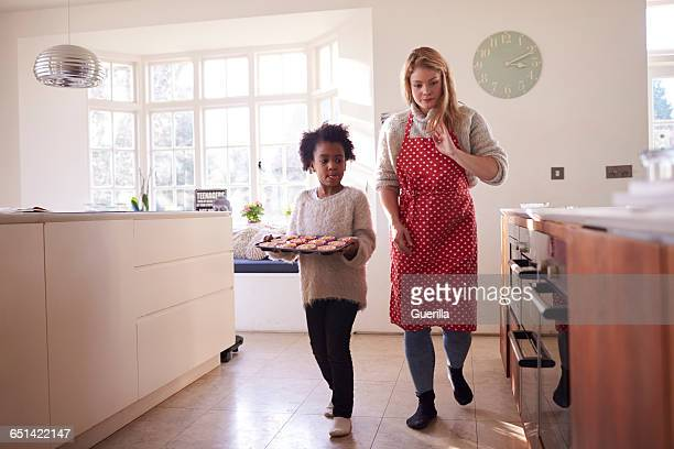 mother and daughter carrying cupcakes ready to put in oven - ウェスト・バークシャー ストックフォトと画像