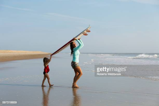 mother and daughter carrying surfboard on beach - virginia beach stock photos and pictures