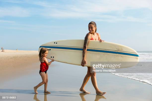 Mother and daughter carrying surfboard on beach