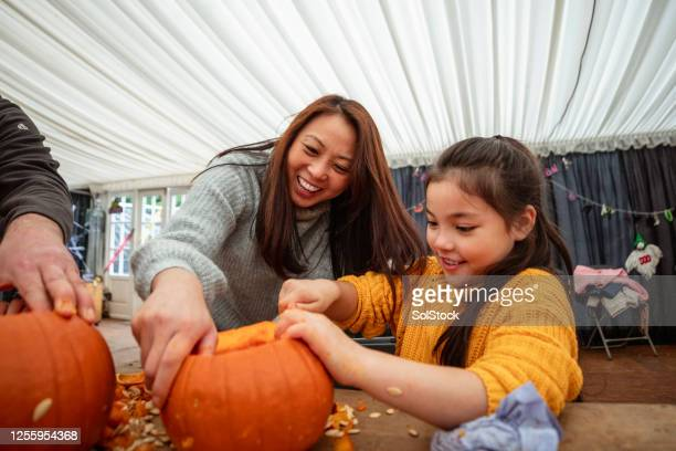 mother and daughter carving pumpkins - carving craft product stock pictures, royalty-free photos & images