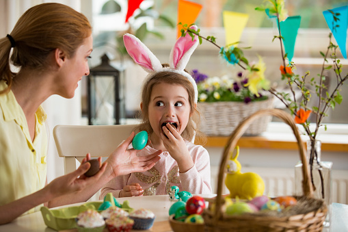 Mother and daughter celebrating Easter, eating chocolate eggs. Happy family holiday. Cute little girl in bunny ears laughing, smiling and having fun. 921672548