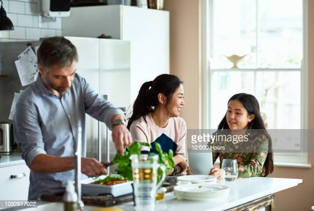 mother and daughter chatting in kitchen as father makes dinner - family at home stock photos and pictures