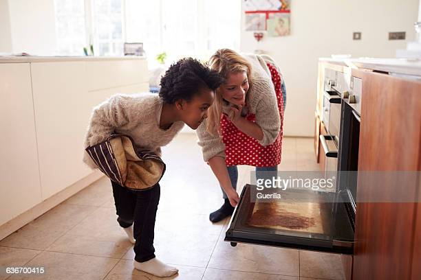 mother and daughter checking cupcakes into oven - ウェスト・バークシャー ストックフォトと画像