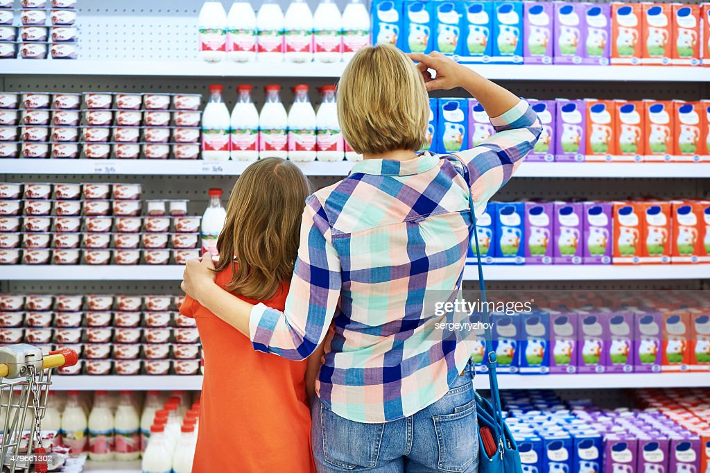 Mother and daughter choosing dairy products : Stock Photo