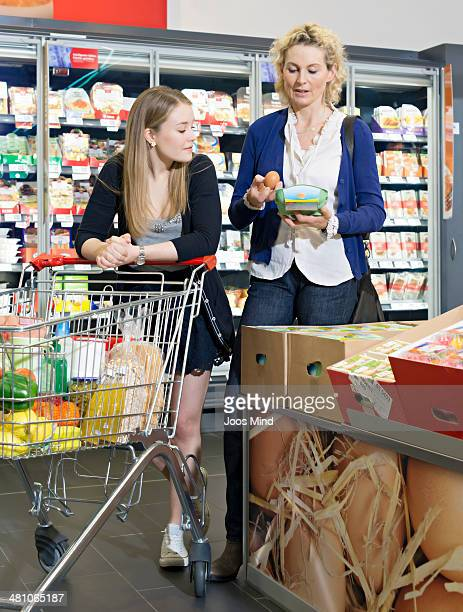 mother and daughter choosing eggs in supermarket