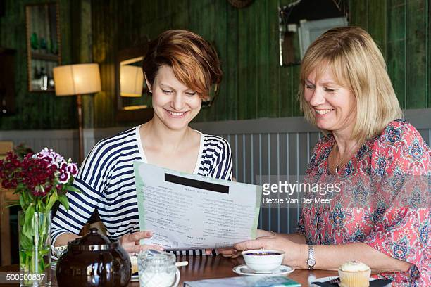 mother and daughter choosing food in cafe.