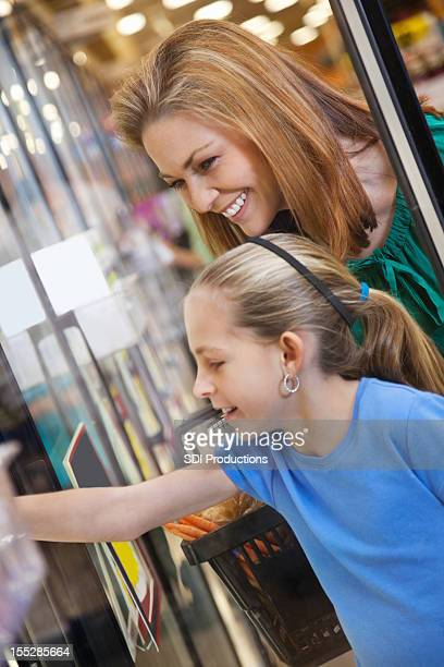 Mother and daughter choosing freezer food at grocery store