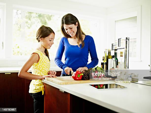 Mother and daughter chopping vegetables in kitchen