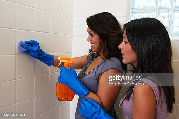 Mother and daughter (13-15) cleaning bathroom, mother cleaning wall